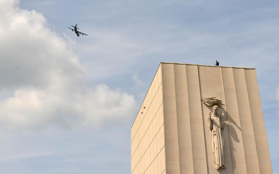 A C-130 of the 86th Airlift Wing out of Ramstein Air Base, Germany, flies over the memorial chapel at Lorraine American Cemetery in St. Avold, France, Sunday, May 26, 2019, during the Memorial Day ceremony held there.