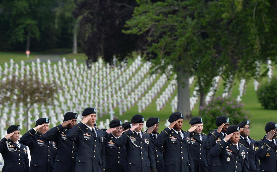 Soldiers of the 2nd Cavalry Regiment out of Vilseck, Germany, salute during the playing of the U.S. and French national anthems during the Memorial Day ceremony at Lorraine American Cemetery in St. Avold, France, Sunday, May 26, 2019.