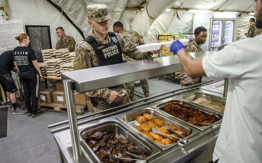 Soldiers deployed to the Polish military base in Powidz are served food at the dining facility, Aug. 27, 2019.
