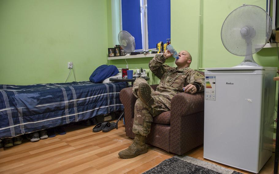Capt. Dustin Martin, the base mayor, sits in his dorm room on a military base in Powidz, Poland, Aug. 27, 2019. He shares the room with two other soldiers.
