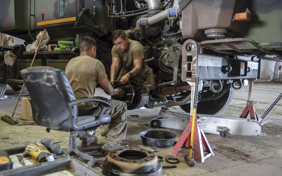 Spc. Sean Hrab, right, and Pfc. Jose Orozzo work on the wheel assembly of a vehicle in the motor pool on a military base in Powidz, Poland, Aug. 27, 2019.