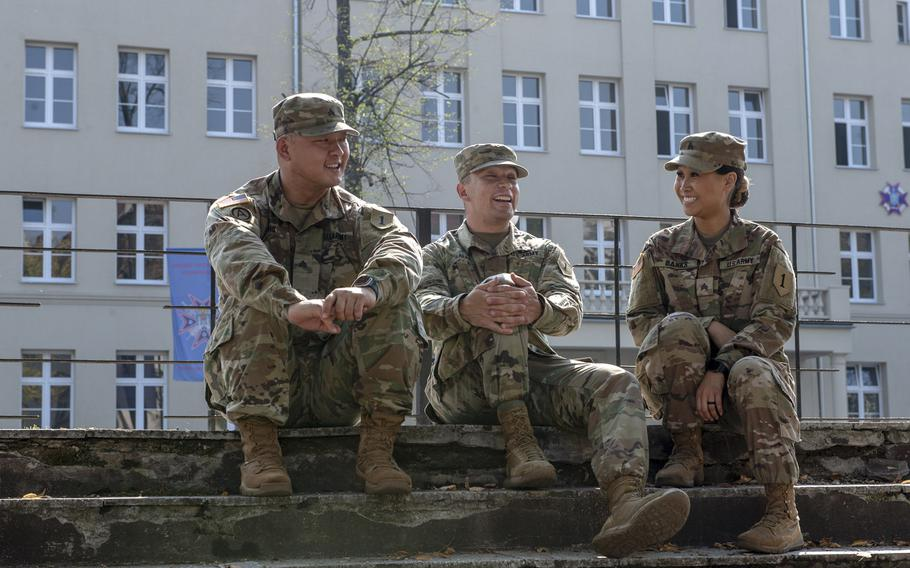 From left, Sgt. Jason Cho, Spc. Joseph Salas and Sgt. Jennie Banks from the 1st Infantry Division sit in front of a newly constructed building on a Polish military base in Poznan, Aug. 28, 2019.