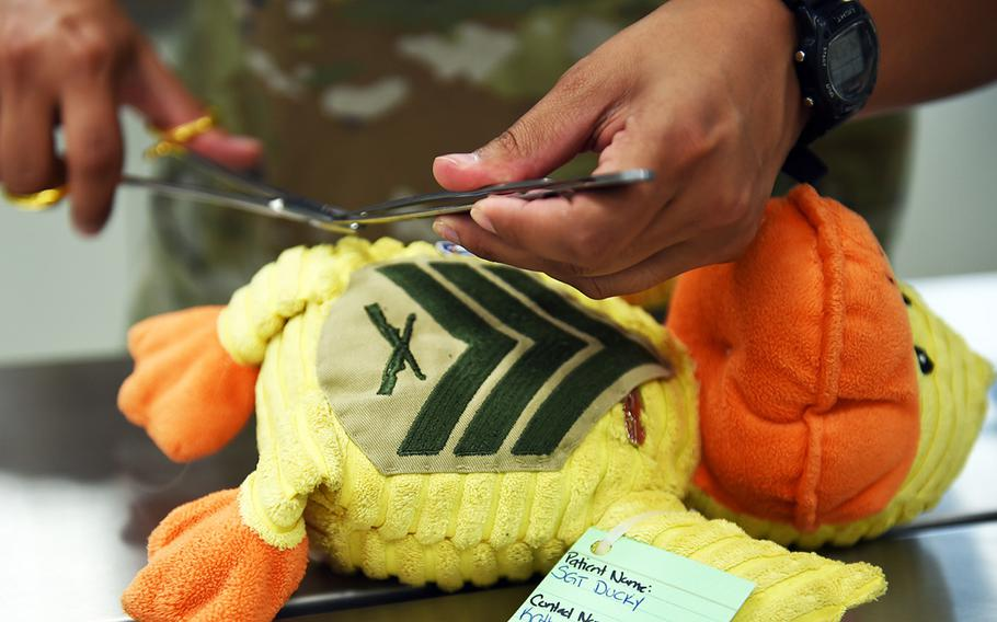 """A stuffed duck, named """"Sgt. Ducky,"""" is operated on at the suture clinic for stuffed animals at Vilseck, Germany, Wednesday, Aug. 28, 2019."""