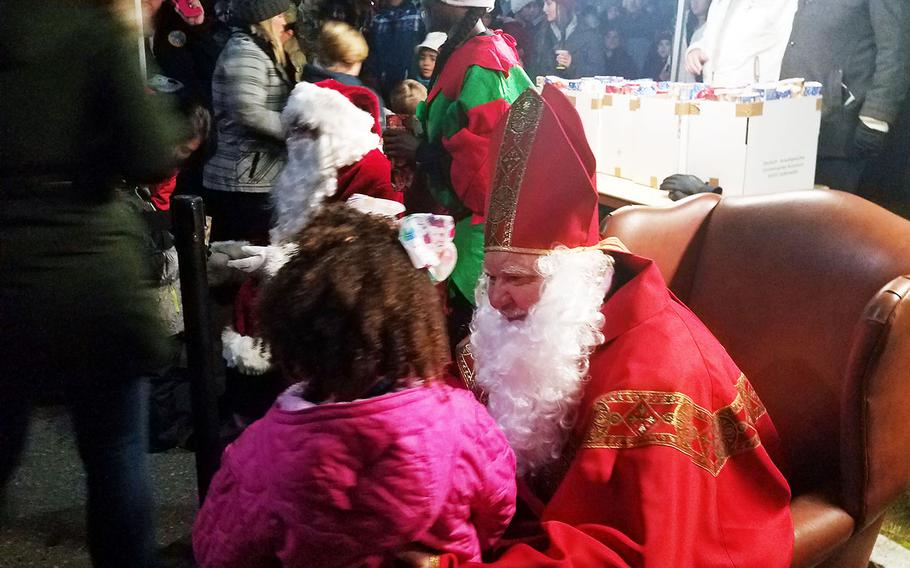 St. Nicholas talks to a little girl during the holiday tree lighting ceremony at Grafenwoehr, Germany, Tuesday, Dec. 3, 2019.