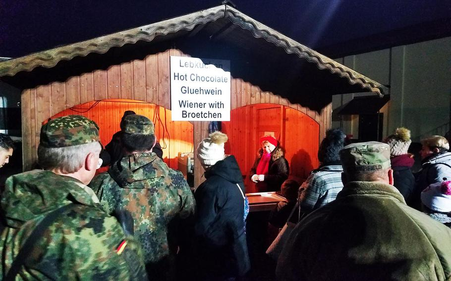 German and American soldiers and family members stand in line to get traditional German Christmas foods and drinks during the holiday tree lighting ceremony at Grafenwoehr, Germany, Tuesday, Dec. 3, 2019.
