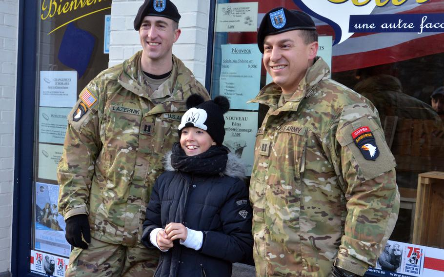 Capt. Jake Lazebnik, left, and Capt. Blake Ritchey of the 101st Airborne Division pose with a young Belgian on the streets of Bastogne, Belgium, Saturday, Dec. 14, 2019. The Screaming Eagles and other service members were in town to mark the 75th anniversary of the World War II Battle of the Bulge.