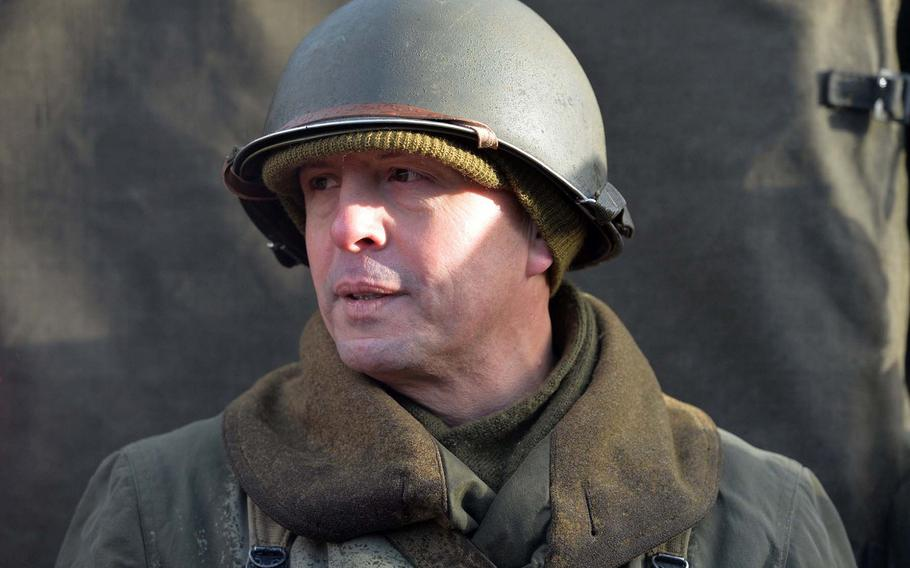 Dressed in World War II-style garb like those worn 30th Infantry Division, Curtis Rhymer, from Kaiserslautern, Germany, talks about the Battle of the Bulge, while visiting Bastogne Barracks in Bastogne, Belgium, during commemorations marking the 75th anniversary of the Battle of the Bulge.