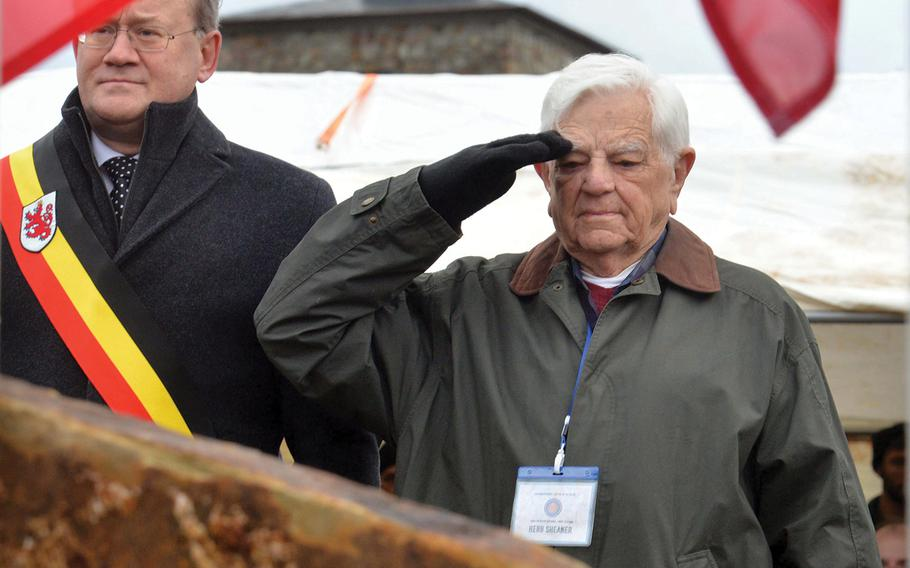Standing next to St. Vith mayor Herbert Grommes, World War II veteran Herb Sheaner salutes after they unveiled a monument to World War II prisoners of war in the St. Vith, Belgium, district of Schoenberg on Sunday, Dec. 15, 2019.