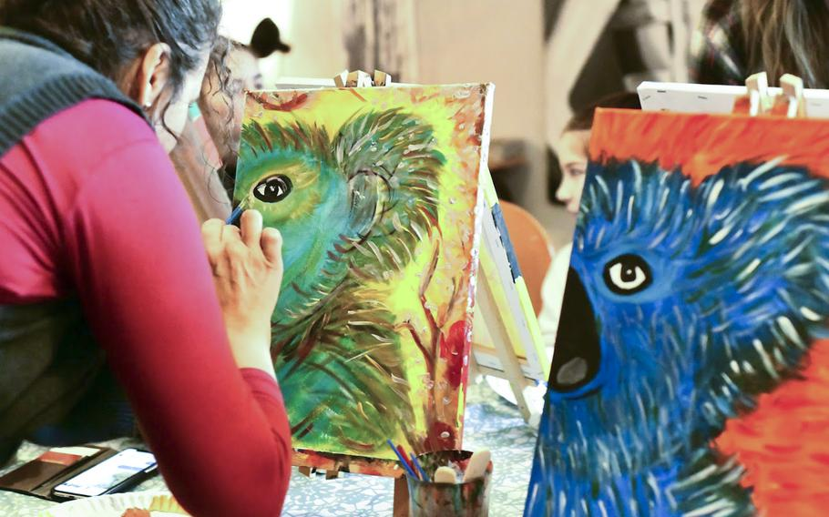 Jizela Dutka-Chirichetti puts the finishing touches on a koala bear against a yellow background on Saturday, Jan. 25, 2020 at artist Beatrice Gentry's studio in Landstuhl, Germany. Dutka-Chirichetti's painting will be auctioned off online to raise money for victims of the Australian bushfires.