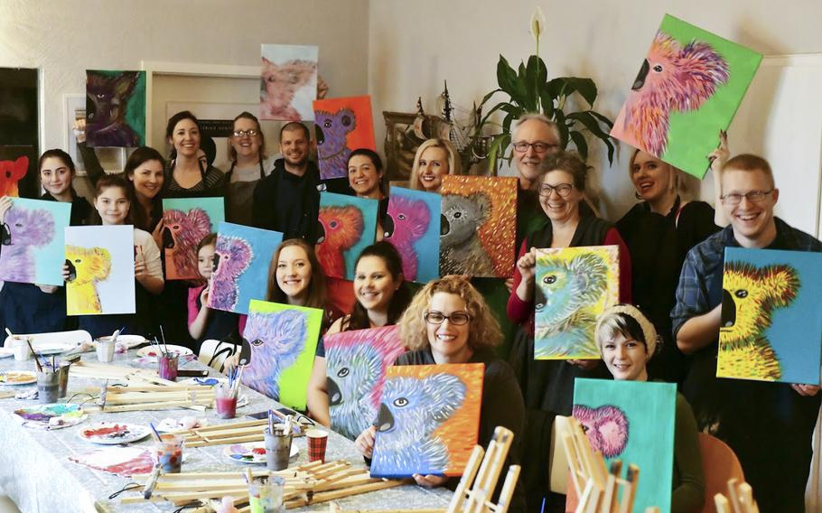 Members of the Kaiserslautern military community hold up their finished paintings of koala bears at a charity event in Landstuhl, Germany, on Saturday, Jan. 25, 2020, to raise money for victims of the Australian bushfires.  The event was organized by Beatrice Gentry, second from right, standing.