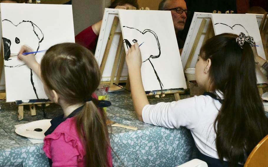 Six-year-old Kat Young, left, and her sister Victoria put the beginning brushstrokes on the koala bears they painted at a fundraiser for victims of the Australian bushfires in Landstuhl, Germany on Saturday, Jan. 25, 2020.