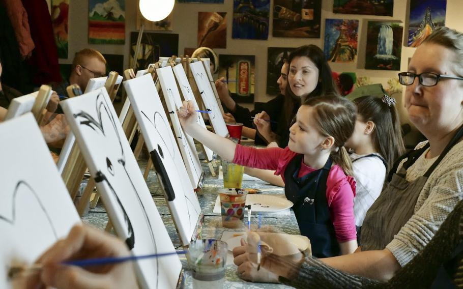 Members of the Kaiserslautern military community  paint the first strokes of koala portraits at a fundraiser for victims of the Australian bushfires, in Landstuhl, Germany, on Saturday, Jan 25, 2020.