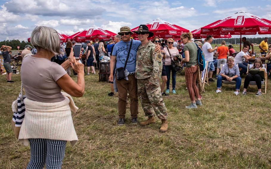 """Capt. Marc Speciale, 278th Armored Cavalry Regiment deployed with Battle Group Poland, poses for pictures with locals during the """"Tank Battle"""" event held at Bemowo Piskie Training Area in Poland, July 13, 2019."""