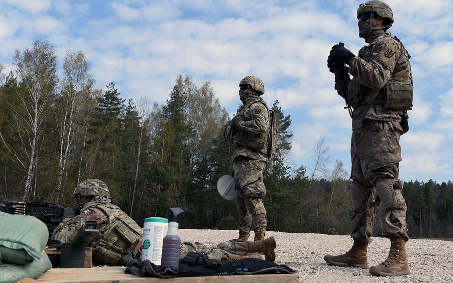 Spc. Nicholas Smith, a fire support specialist with the 41st Field Artillery Brigade, left, fires an M240B machine gun as Sgt. Eamonn Duggan, center, and Spc. Luis Garcia, right, observe during an exercise at Grafenwoehr Training Area, Germany, April 17, 2020.