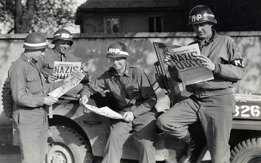 Four military policemen take a break along a German road to read in The Stars and Stripes newspaper about the Nazi surrender, ending World War II in Europe.