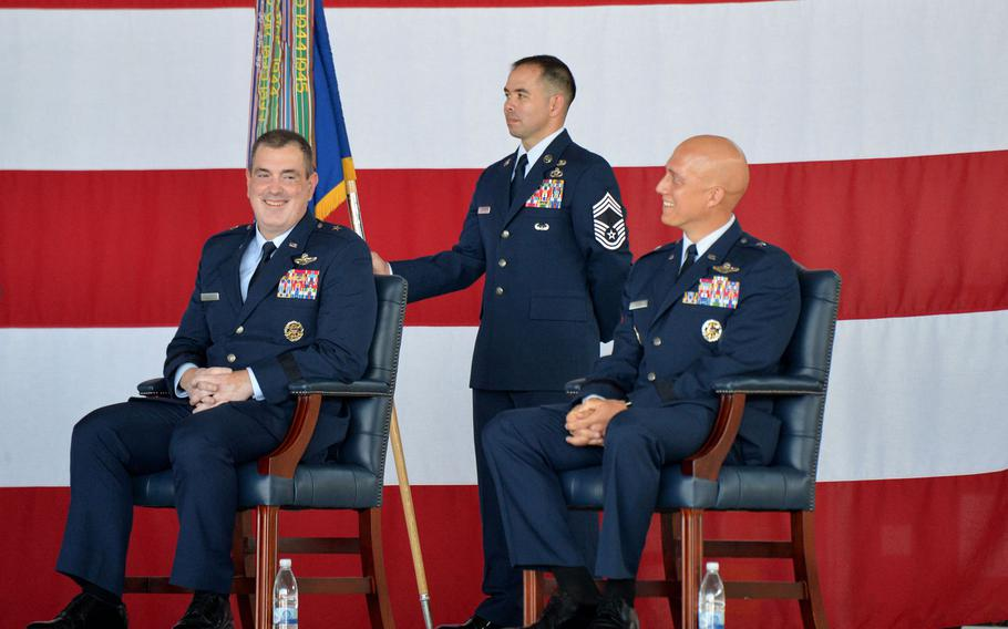 Outgoing 86th Airlift Wing commander Brig. Gen. Mark R. August, left, and incoming commander Brig. Gen. Joshua Olsen chuckle during a speech by 3rd Air Force commander Maj. Gen. Ronald Reed, at the 86th's change of command ceremony at Ramstein Air Base, Germany, Aug. 7. 2020. At center is Chief Master Sgt. Tommy Childers with the unit guidon.
