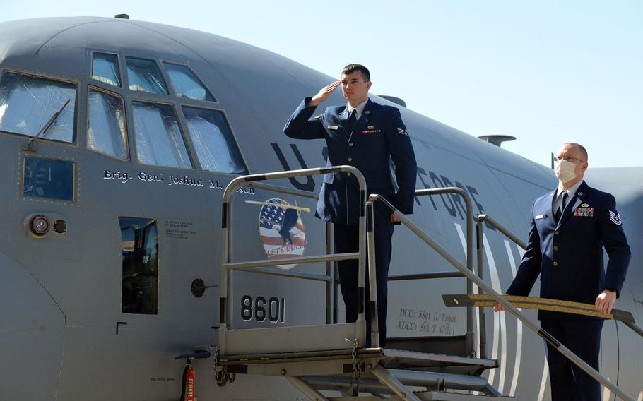 Senior Airman Trevor Gillett salutes the new commander of the 86th Airlift Wing, Brig. Gen. Josh M. Olsen after unveiling his name on a C-130 aircraft during the unit's change of command ceremony at Ramstein Air Base, Germany, Aug. 7, 2020. At right, Tech. Sgt. Sean Taylor holds the nameplate of the outgoing commander, Brig. Gen. Mark R. August.