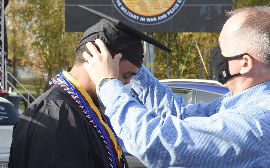 George ReGester adjusts the cap of his son, Stedman ReGester, 21, at the University of Maryland Global Campus Europe commencement ceremony for the class of 2020 on Saturday, Nov. 7, 2020, in Kaiserslautern, Germany. Stedman, who lives in Ansbach, Germany, with his family, received a bachelor's degree in networking security.