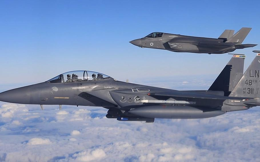 A U.S. Air Force F-15E Strike Eagle from RAF Lakenheath, foreground, and a U.K. F-35B Lightning II from RAF Marham fly in formation in November 2018. Acting Secretary of Defense Christopher C. Miller lauded U.K. plans to give its military the largest spending boost it has seen in 30 years.