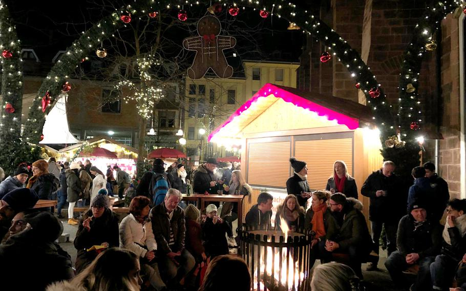 A crowd sits around an open fire near the Stiftskirche in Kaiserslautern, Germany, during the 2019 Christmas market. Most Christmas markets in Germany have been canceled because of the coronavirus and large gatherings have been banned, but Germany has temporarily lifted a travel ban on Americans to allow the children of  service members, Defense Department civilian employees and others covered by the Status of Forces Agreement and assigned to Germany to enter the country over the holidays.