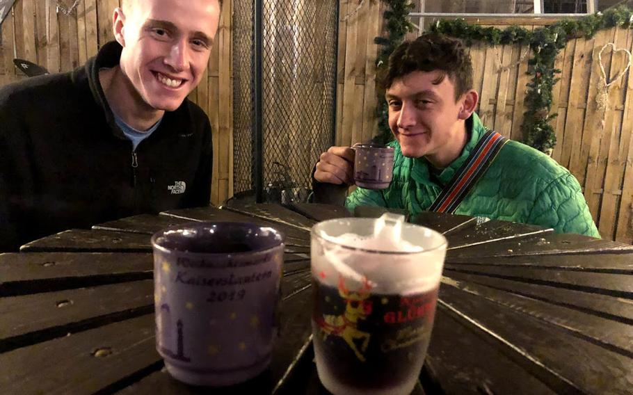 Air Force Academy cadets Luca Zeitvogel, left, and Marcos Ferreira sample gluehwein at the Christmas market in Kaiserslautern, Germany, on Dec. 18, 2019. Germany has partially lifted a months-old coronavirus travel ban on Americans to allow U.S. children whose parents have SOFA status and are assigned to the country to visit over the holidays. They will have to abide by local coronavirus rules, including quarantine and mask-wearing, and most Christmas markets will be closed.