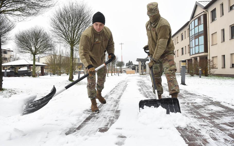 Airmen 1st Class David Camargo, 24, left, and Raylan Sherwood, 21, shovel snow outside their dormitory at Ramstein Air Base, Germany, on Tuesday, Dec. 1, 2020. It was the first snowfall of the season for military bases in the Kaiserslautern area.