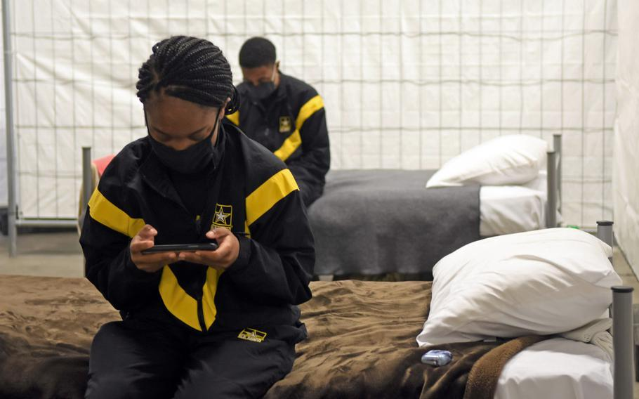 Army Pfc. Cherisse Bishop, foreground, and Sgt. Brithany Joseph check their devices while resting on their cots inside the quarantine facilities at Rhine Ordnance Barracks in Kaiserslautern, Germany, Nov. 12, 2020. Newly arriving soldiers wear Army physical training gear to make them visibly distinct from other soldiers who are further along in the quarantine process.