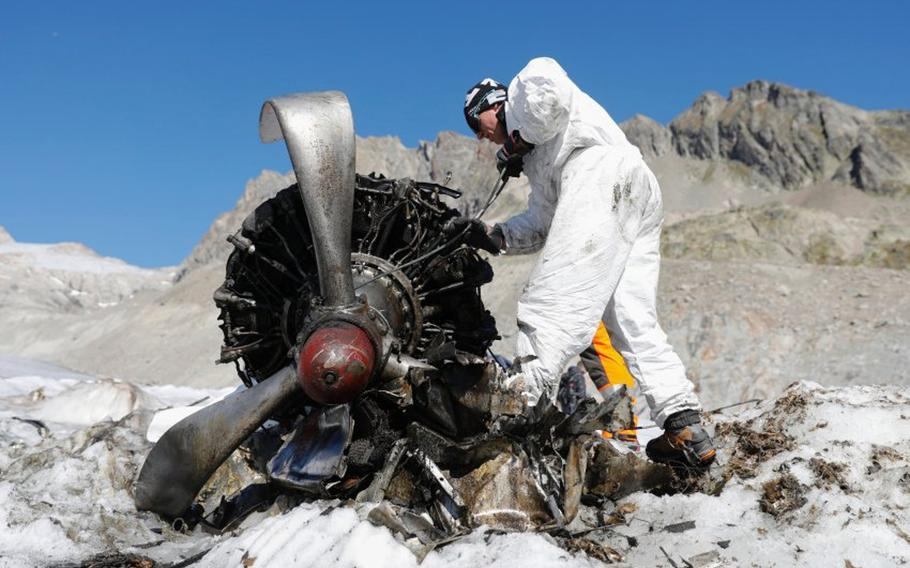 A Swiss soldier works on an engine of a U.S. C-53 Skytrooper that emerged from the ice of the Gauli Glacier in Switzerland in 2018, more than 70 years after the plane crash-landed at the top of the glacier in Nov. 1946. Analysis of ice samples collected from the glacier in 2019 led a scientist to update predictions of where and when the plane's fuselage will emerge from the ice.