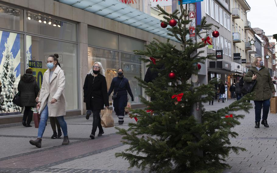 Shoppers walk in downtown Kaiserslautern, Germany, on Dec. 14, 2020, two days before tougher coronavirus restrictions are implemented in Germany.