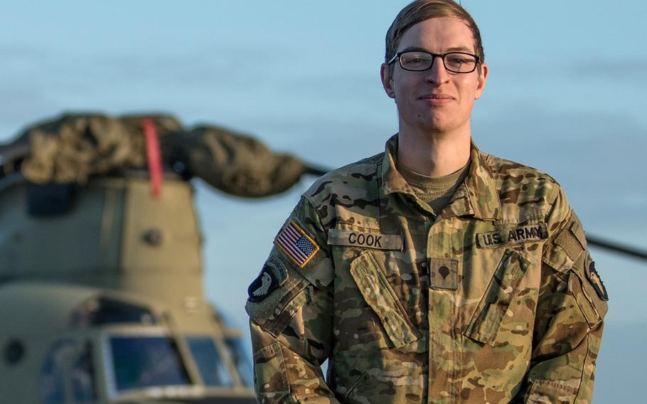 Army Spc. Bruce Cook, a CH-47F Chinook crew chief, stands in front of a helicopter at Storck Barracks in Illesheim, Germany, Dec. 16, 2020. Cook was was the one that initially witnessed a car accident from the air while flying back to Illesheim from a routine training mission. The Chinook landed in a field to provide medical assistance to the accident victim.