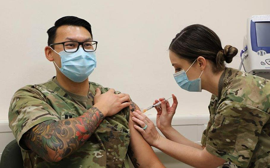 Capt. Joey Nguyen, a nurse assigned to 2nd Cavalry Regiment, receives the Moderna COVID-19 vaccine from Capt. Breslin Gillis at the Soldier Readiness Processing Center, Rose Barracks, Vilseck, Germany, Dec. 28, 2020.
