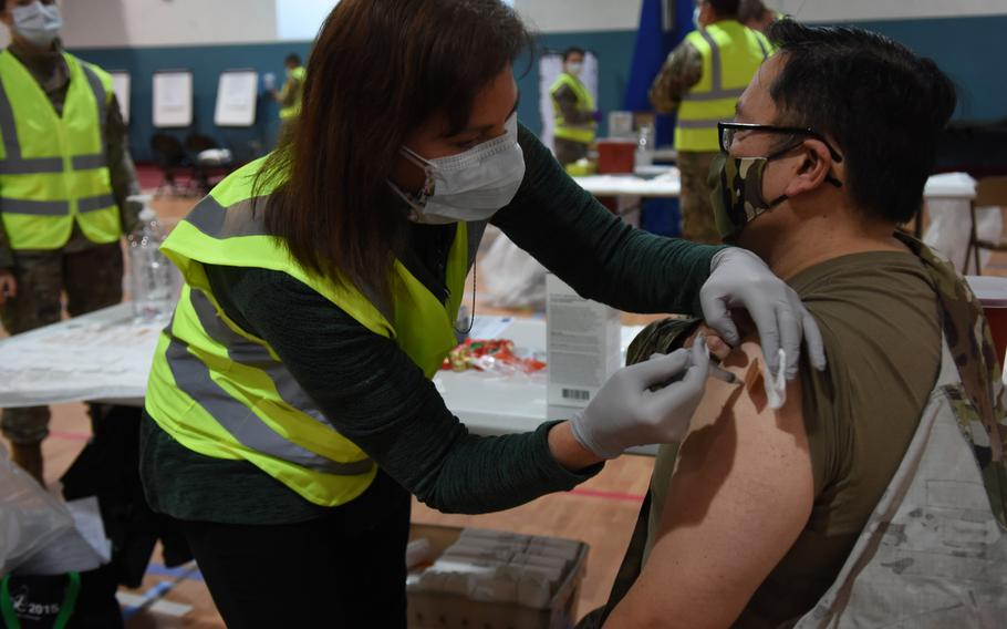 Sarah Lewis, a registered nurse with the 86th Medical Group, vaccinates Col. Ryan Mihata, the 86th Medical Group commander, at Ramstein Air Base, Germany, on Monday, Jan. 4, 2021, against the disease caused by the coronavirus.