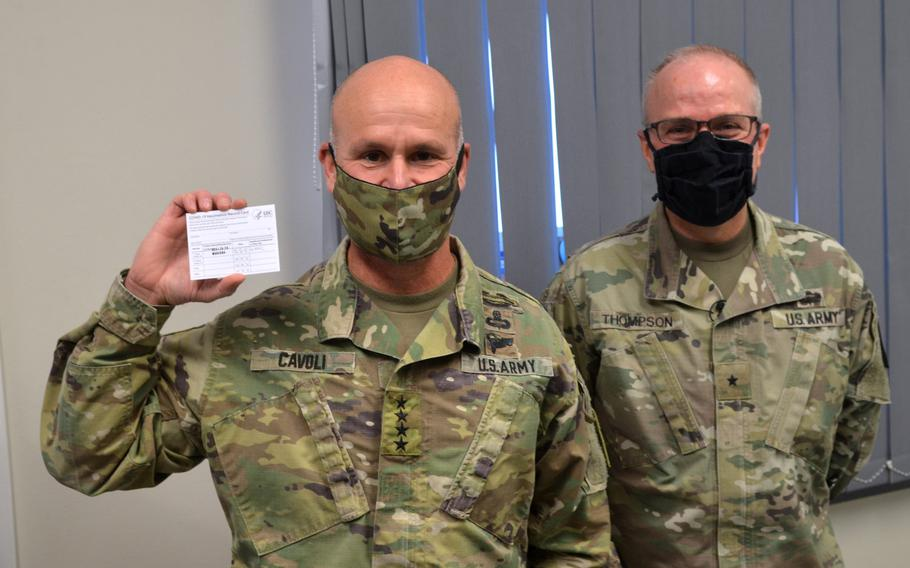 Gen. Christopher G. Cavoli, commander of U.S. Army Europe and Africa, holds up a COVID-19 vaccination card while standing next to Brig. Gen. Mark Thompson, commanding general of Regional Health Command Europe, at the Wiesbaden Army Health Clinic, Germany, Jan. 14, 2021.