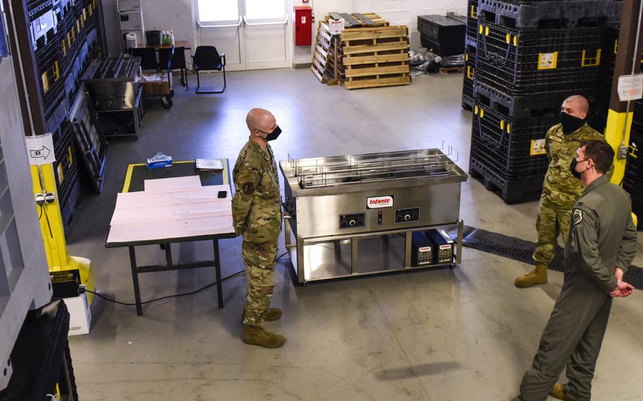 Two members of the 52nd Logistics Readiness Squadron show Col. David C. Epperson, 52nd Fighter Wing commander, bottom right, an ultrasonic weapons cleaner at Spangdahlem Air Base, Germany, Nov. 9, 2020.