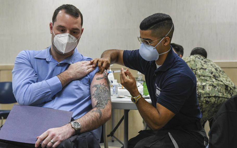 Joseph Rottier, a Defense Department civilian, receives a COVID-19 vaccination from Seaman Victor Rosario at U.S. Naval Support Activity Naples, Italy, Jan. 12, 2021. The Navy base began offering vaccinations to the general U.S. base population Thursday, Jan. 27.