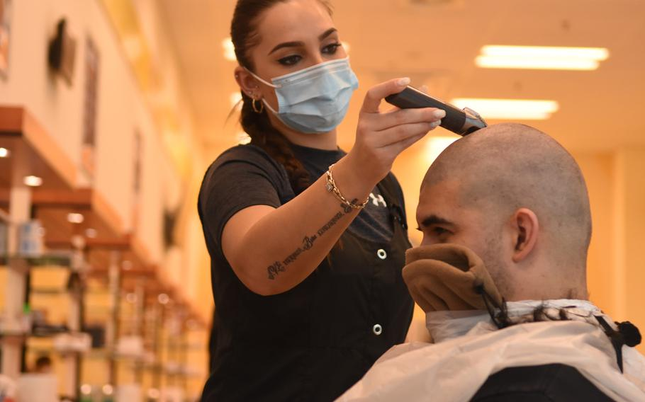 Kaltrian Ibrij shaves off Senior Airman Jeremiah Lamb's hair at the barbershop on Ramstein Air Base, Germany, in May 2020, when it had just reopened after being closed for about six weeks during the first wave of the coronavirus pandemic. Barbershops and beauty salons on U.S. military bases in Germany were closed again in December because of the virus, but will reopen March 1.