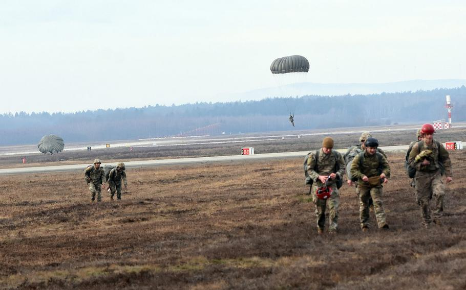 Paratroopers walk on the airfield at Ramstein Air Base, Germany, after completing a jump on Thursday, Feb. 18, 2021.