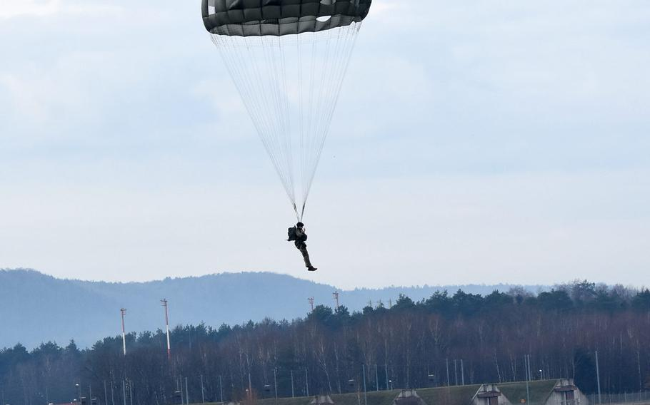 A paratrooper descends onto a grassy area inside the airfield at Ramstein Air Base, Germany, on Thursday, Feb. 18, 2021. Thirty paratroopers from Air Force and Army units in Germany jumped at Ramstein following a short-notice request from the 435th Contingency Response Group to use the airfield after several jumps were canceled due to poor weather and coronavirus restrictions.