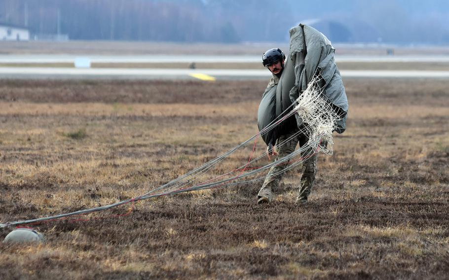 Tech. Sgt. Dwight Stalter of the 435th Contingency Response Group at Ramstein Air Base, Germany, folds his parachute after landing at the base's airfield on Thursday, Feb. 18, 2021.