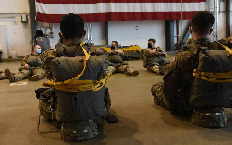 Paratroopers sit with their gear inside a hangar at Ramstein Air Base, Germany, before a jump on Feb. 18, 2021. About 30 paratroopers from Army and Air Force units in Germany had the rare chance to jump at Ramstein's busy airfield to maintain their jump requirements.