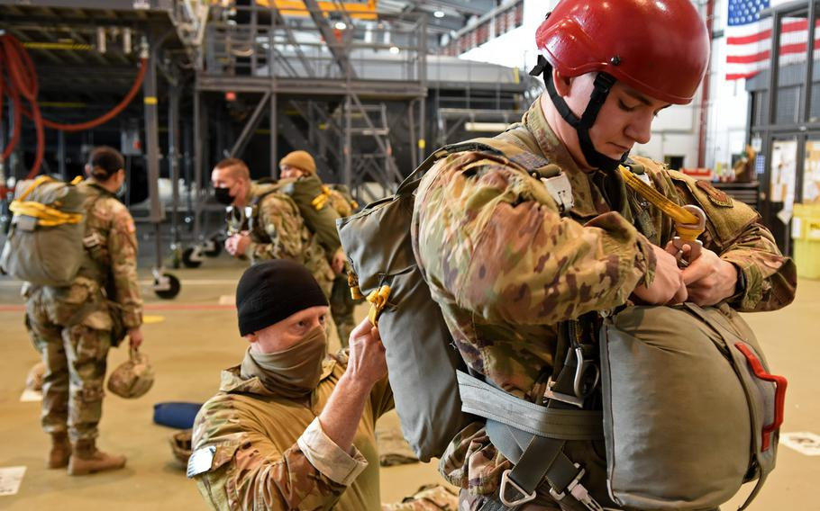 Air Force Master Sgt. Jim Burke, an airfield manager and jump master with the 435th Contingency Response Group at Ramstein Air Base, Germany, ensures Senior Airman Cody Paynter's parachute equipment is secure and ready to go before a rare jump Thursday, Feb. 18, 2021, at Ramstein.