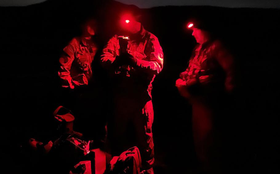 Chief Warrant Officer 3  Elliott Boiles, a maintenance test pilot with the 101st Combat Aviation Brigade, left, and Chief Warrant Officer 2 Sean Deegan, a pilot with the brigade, center, prepare for hoist operations during exercise Combined Resolve at Hohenfels, Germany, Feb. 17, 2021.