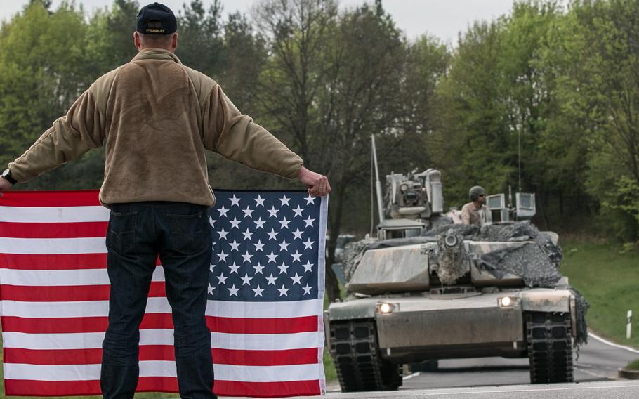 A German holding an American flag greets U.S. vehicles assigned to the 2nd Armored Brigade Combat Team, 1st Infantry Division as they move from Grafenwoehr Training Area to Hohenfels, Germany, in 2018. Germany contributed $118 million to support foreign troop missions in the country in 2020.