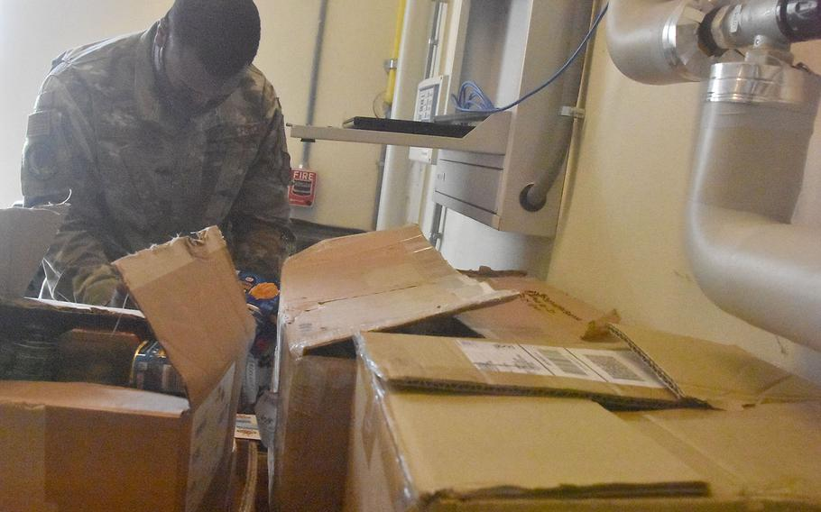 Staff Sgt. James Harris looks through almost two dozen boxes of nonperishable food items donated by those attached to Aviano Air Base, Italy. The 26-year-old Georgia native spearheaded the drive through the African American Heritage Committee on base and donated more than 1,100 items to the local branch of the Italian Red Cross.