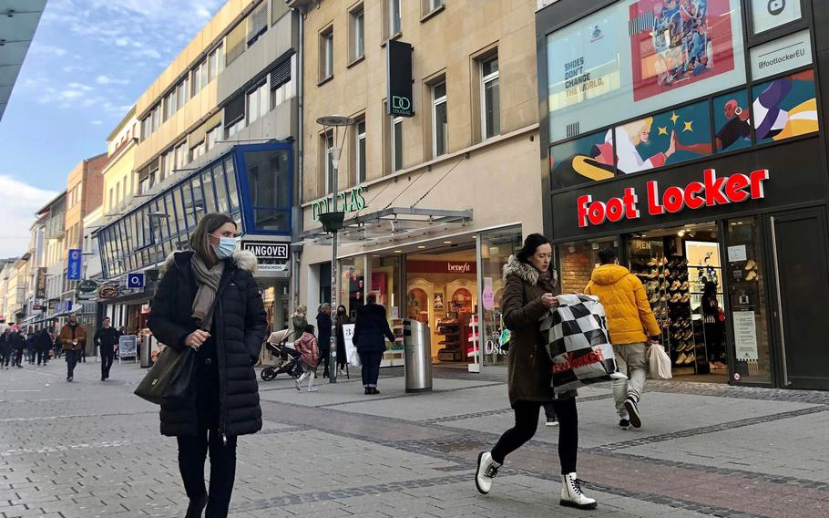People walk through the pedestrian shopping district in Kaiserslautern, Germany, on March 23, 2021. Customers will require an appointment to shop in-person in Kaiserslautern county starting Tueday, March 31, 2021, after officials tightened coronavirus restrictions following a spike in new infections.