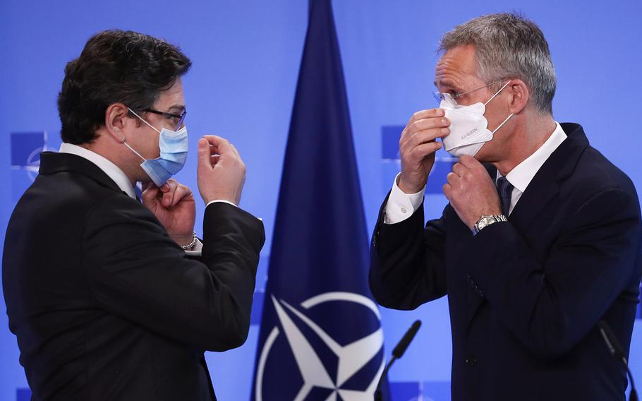 NATO Secretary General Jens Stoltenberg, right, and Ukraine's Foreign Minister Dmytro Kuleba put on their protective face masks after addressing a media conference at NATO headquarters in Brussels, Tuesday, April 13, 2021. Stoltenberg and Kuleba met to discuss Russia's troop buildup troops along the frontier with Ukraine.
