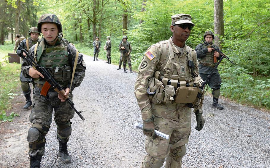 U.S. Army Staff Sgt. Gregory Simmons, center, supervises Ukrainian national guardsmen on a simulated patrol in July 2015, at a training facility in Yavoriv, Ukraine. A rapid Russian military buildup along the Ukrainian border in recent weeks has sparked fears of an invasion.