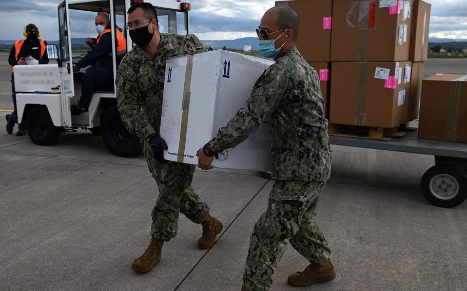 Chief Petty Officer Wilder Fermangomez, left, and Petty Officer1st Class Rolando Sol, Defense Logistics Agency Distribution Sigonella, carry COVID-19 vaccines headed for the aircraft carrier USS Dwight D. Eisenhower from Naval Air Station Sigonella, Italy, in March 2021. More doses should arrive soon following a slow start to the Europe vaccination campaign, U.S. European Command's Gen. Tod Wolters told Congress on April 15, 2021.