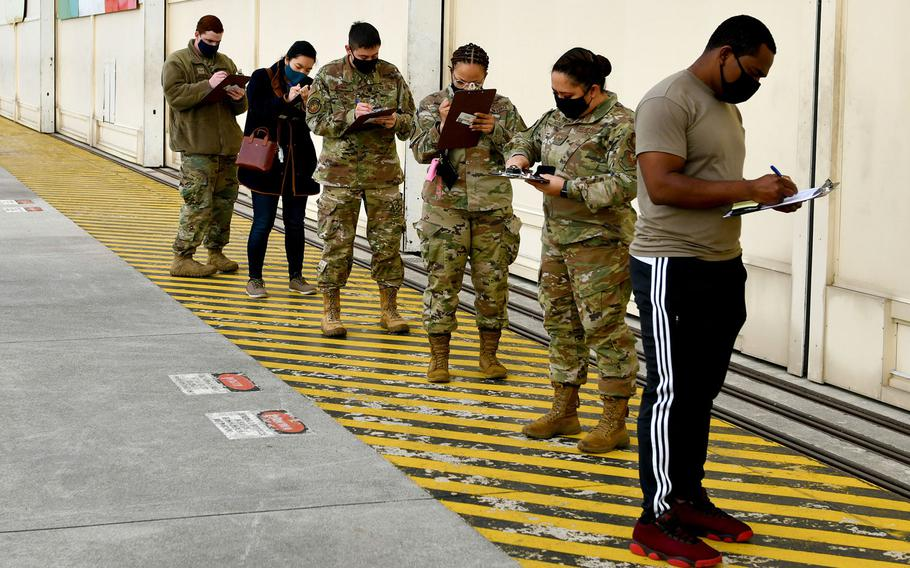 U.S. airmen and dependents fill out paperwork prior to receiving COVID-19 vaccinations at Aviano Air Base, Italy, April 23, 2021.