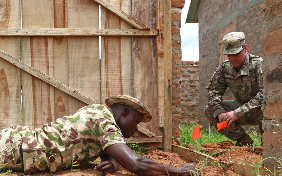U.S. Army Staff Sgt. Brian Miller, an explosive ordnance technician, watches while a Nigerian soldier searches for a potential explosive during training at the Nigerian Army School of Military Engineers in Makurdi, Nigeria in May 2019. The country's president, Muhammadu Buhari, asked U.S. Secretary of State Antony Blinken during a virtual meeting April 27, 2021, to move U.S. Africa Command headquarters to Africa.